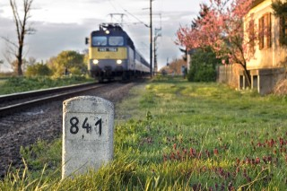 Milestone with old house and train